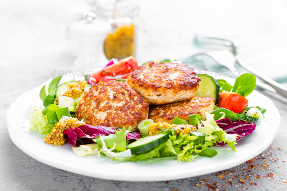 Cutlets and fresh vegetable salad on white plate. Fried meatballs with vegetable salad - Stock Photo - Images