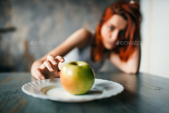 Female hand reaches plate with apple - Stock Photo - Images