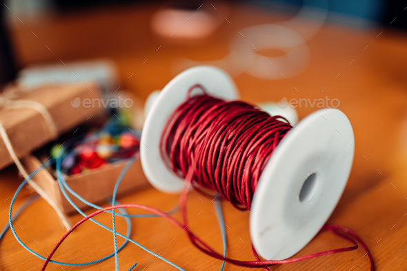 Needlework, coil with red decorative rope, closeup - Stock Photo - Images