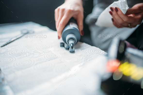 Female tattooist hands holds tattoo machine - Stock Photo - Images