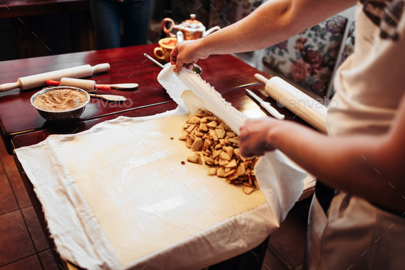 Chef wraps the filling into dough, apple strudel - Stock Photo - Images