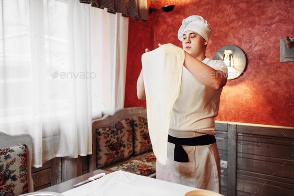Chef in apron and hat making dough on the kitchen - Stock Photo - Images