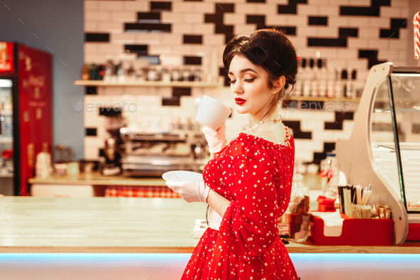 Glamour pin up girl drinks coffee in retro cafe - Stock Photo - Images