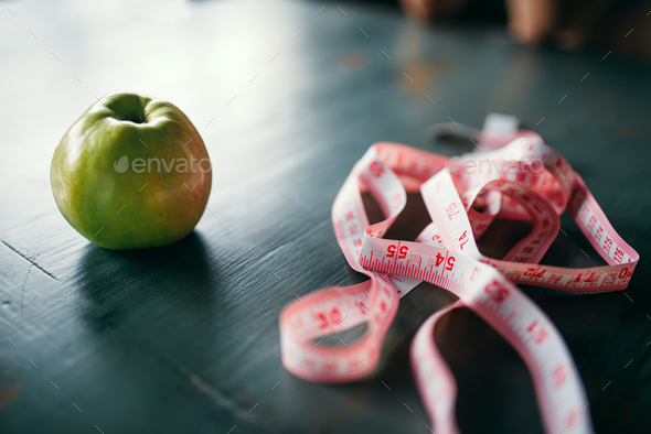 Apple and pink measuring tape, weight loss concept - Stock Photo - Images