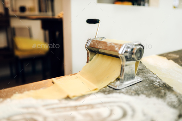 Pasta machine with dough on wooden kitchen table - Stock Photo - Images