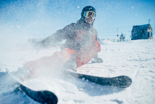 Skier lies on snowy surface of speed slope - Stock Photo - Images