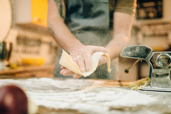 Male chef cooking dough and prepares pasta machine - Stock Photo - Images