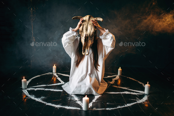 Woman holds skull of the animal in hand, occultism - Stock Photo - Images