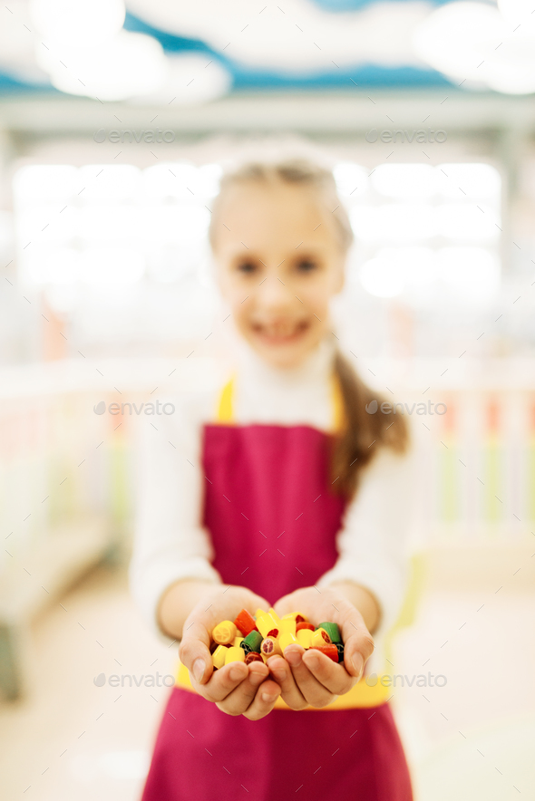 Little girl holds in hands handmade caramel sweets - Stock Photo - Images