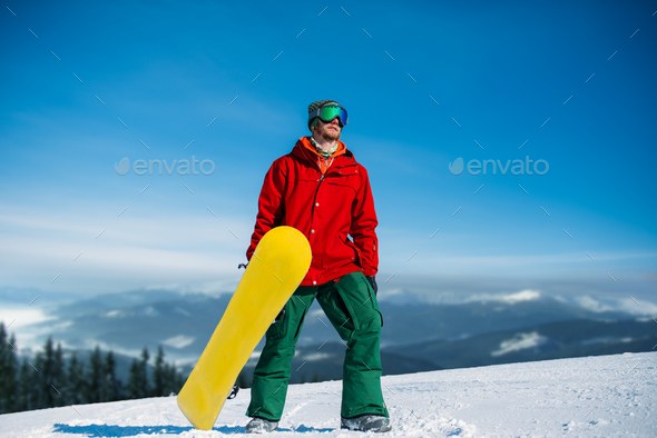 Snowboarder in glasses poses with board in hands - Stock Photo - Images