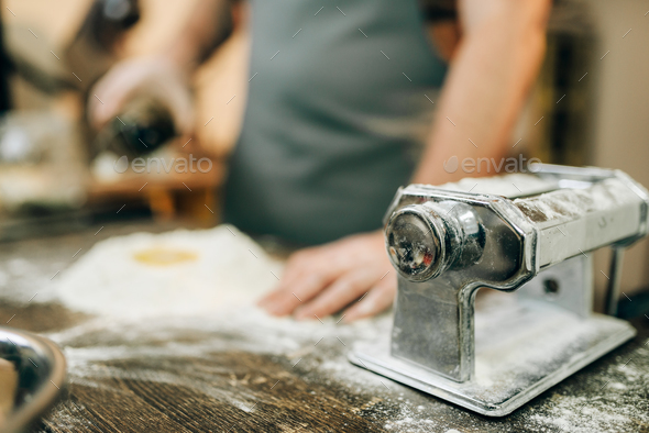 Pasta machine, male chef preparing dough - Stock Photo - Images