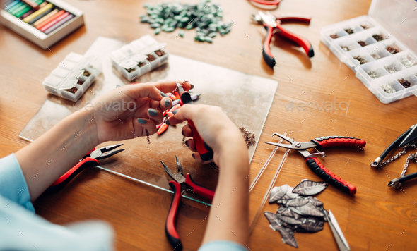 Female person holds pliers, bijouterie making - Stock Photo - Images