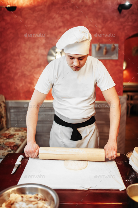 Male chef roll out the dough with a rolling pin - Stock Photo - Images