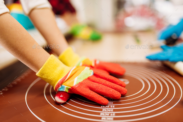 Childrens hands in gloves, caramel making - Stock Photo - Images