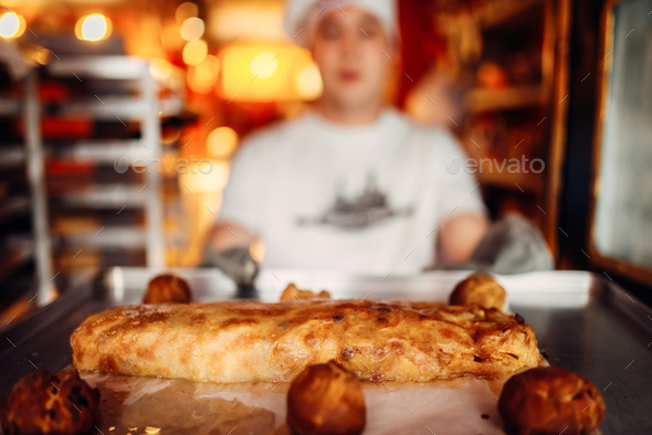 Chef holds baking sheet with fresh cooked strudel - Stock Photo - Images