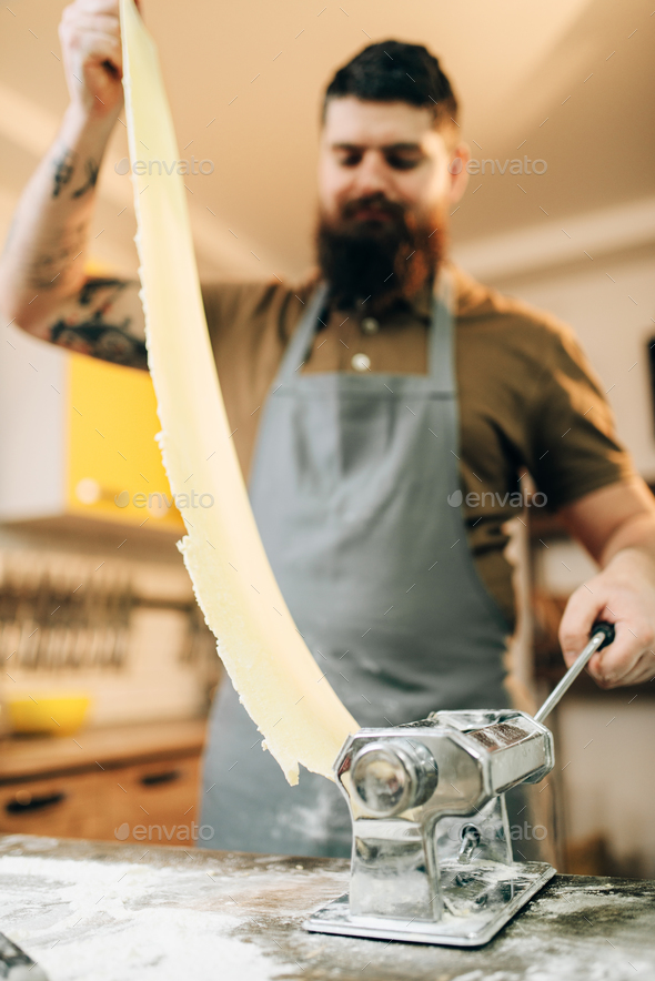 Bearded chef works with dough in pasta machine - Stock Photo - Images