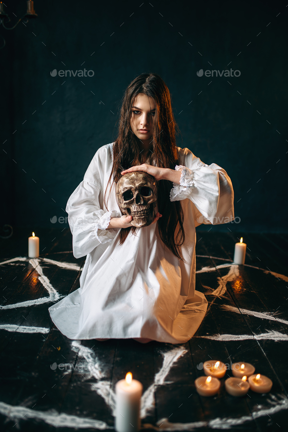 Woman holds human skull in hand, dark magic, witch - Stock Photo - Images