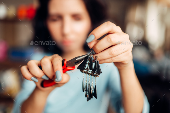 Female master with pliers making handmade earrings - Stock Photo - Images