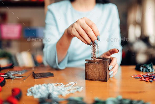 Female hands pulls out metal chain from box - Stock Photo - Images