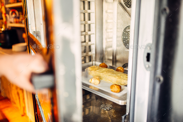 Apple strudel on metal baking sheet in the oven - Stock Photo - Images