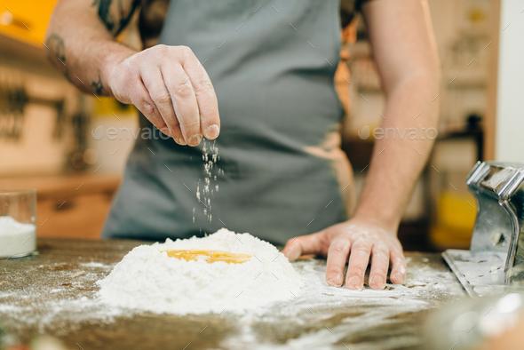 Homemade pasta cooking, man preparing dough - Stock Photo - Images
