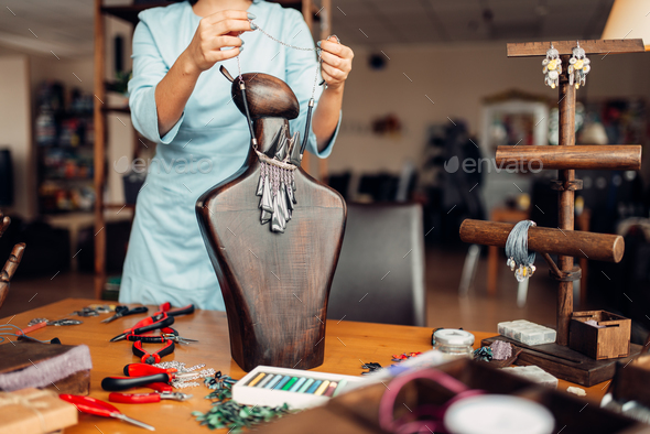 Female person trying on necklace on mannequin - Stock Photo - Images