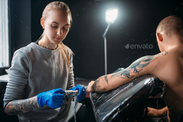 Tattooist makes tattoo by machine on male shoulder - Stock Photo - Images