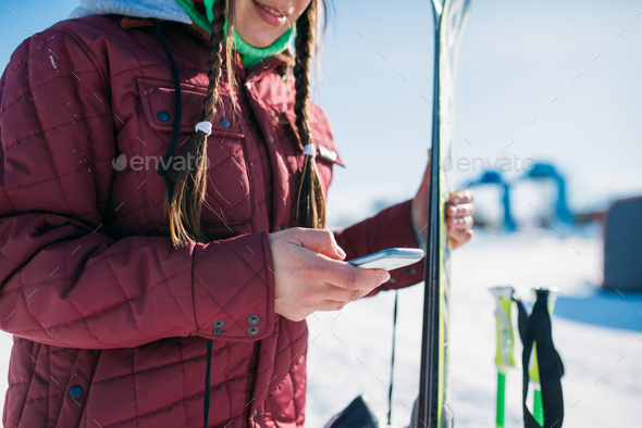 Female skier holds skis and mobile phone in hands - Stock Photo - Images