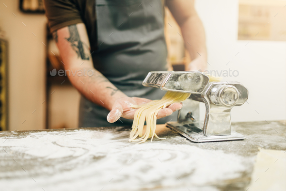 Male chef cooking fettuccine in pasta machine - Stock Photo - Images