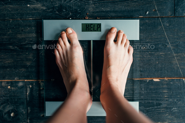 Female feet on the scales with inscription help - Stock Photo - Images