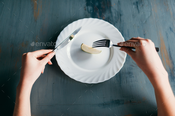 Female person against plate with a slice of apple - Stock Photo - Images