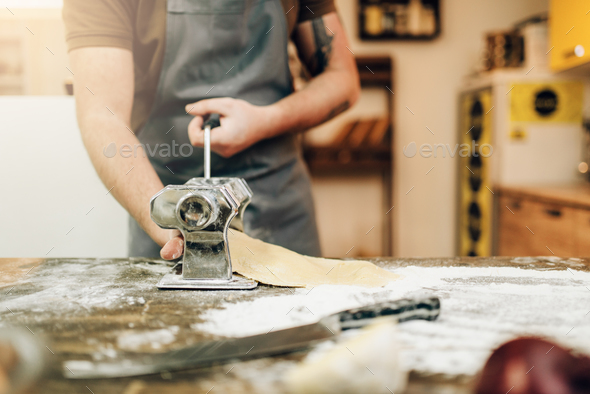 Male chef in apron works with pasta machine - Stock Photo - Images