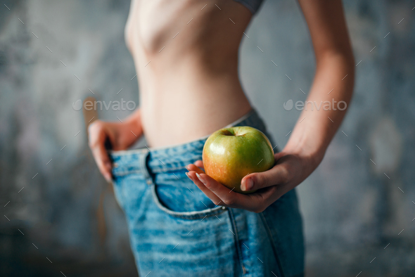 Woman with apple in hand tries on big size jeans - Stock Photo - Images