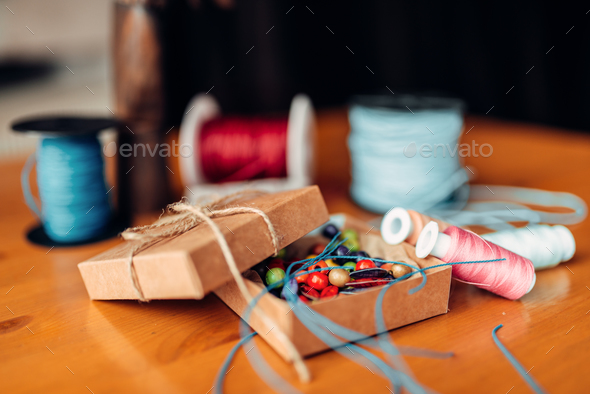 Needlework, box with beads on wooden table - Stock Photo - Images