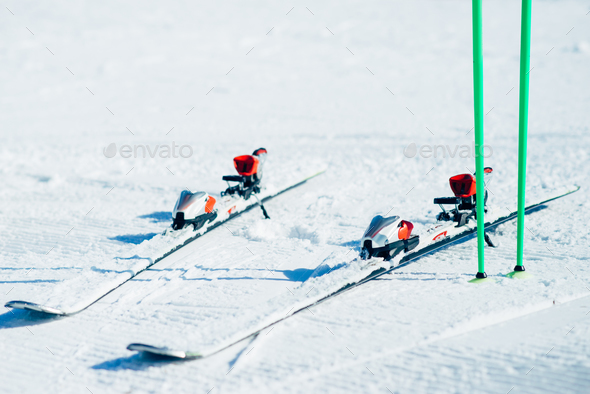 Skis and poles sticking out of the snow closeup - Stock Photo - Images