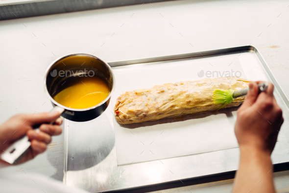 Chef hand lubricates strudel with egg and butter - Stock Photo - Images