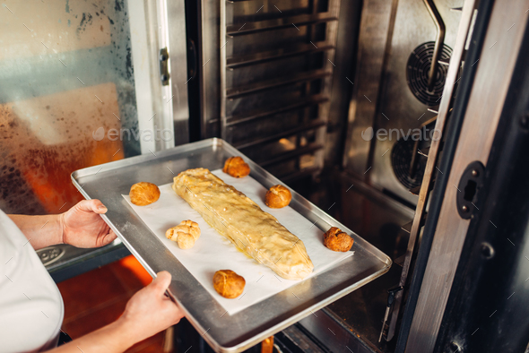 Chef puts strudel on baking sheet in the oven - Stock Photo - Images