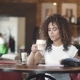 Young Girl Mulatto Drinks Coffee. Beautiful Hispanic Woman Enjoys the Latte in a Cozy Cafe. Portrait - VideoHive Item for Sale