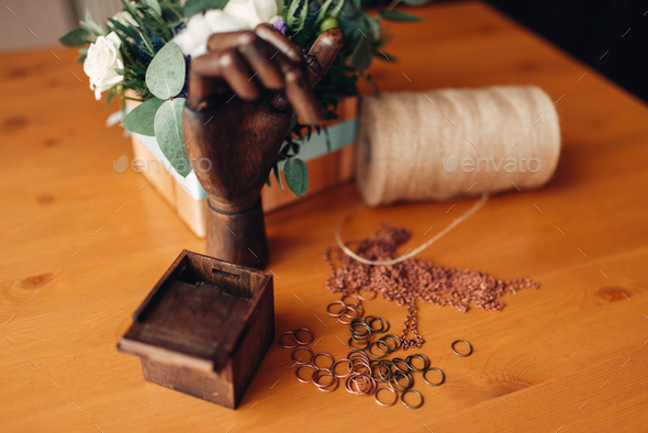 Needlework, metal rings and wooden hand on table - Stock Photo - Images