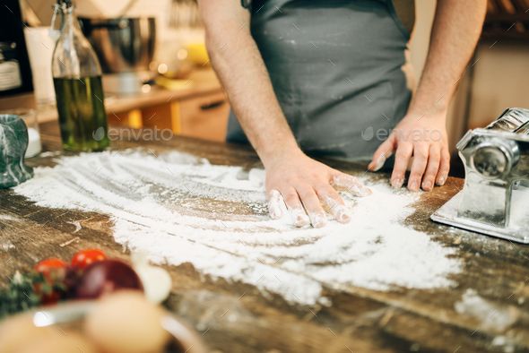 Chef in apron, flour,eggs, pasta machine on table - Stock Photo - Images