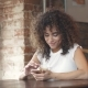 Attractive Hispanic Girl Using Smartphone and Smiles in a Coffee House. - VideoHive Item for Sale