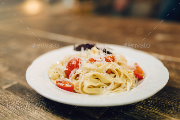 Plate with fresh cooked pasta on wooden table - Stock Photo - Images