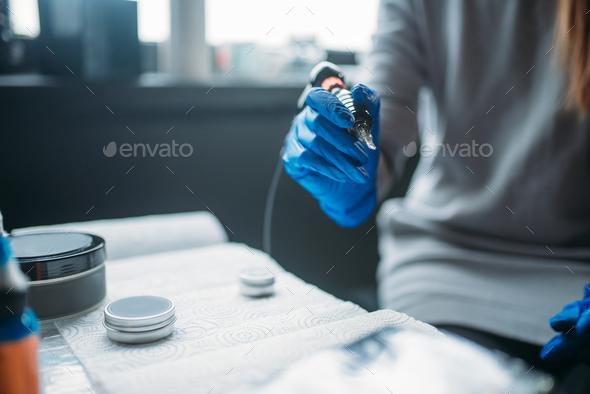 Tattooist holds tattoo machine in hand, tattooer - Stock Photo - Images