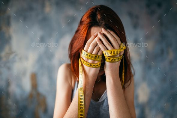 Woman covers face, hands tied with measuring tape - Stock Photo - Images