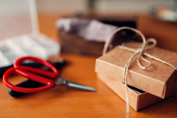 Needlework gift and scissors on wooden table - Stock Photo - Images