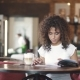 Young Girl Mulatto Drinks Coffee in a Cafe and Looks at the Menu. Beautiful Hispanic Woman Enjoys - VideoHive Item for Sale