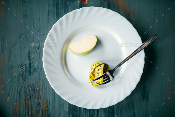 Plate with apple and measuring tape, weight loss - Stock Photo - Images