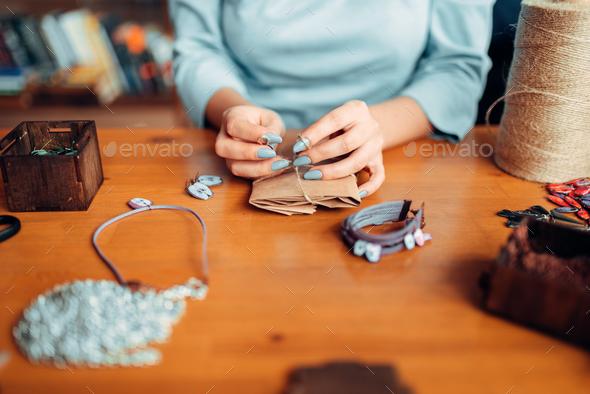 Female master with scissors makes handmade earring - Stock Photo - Images
