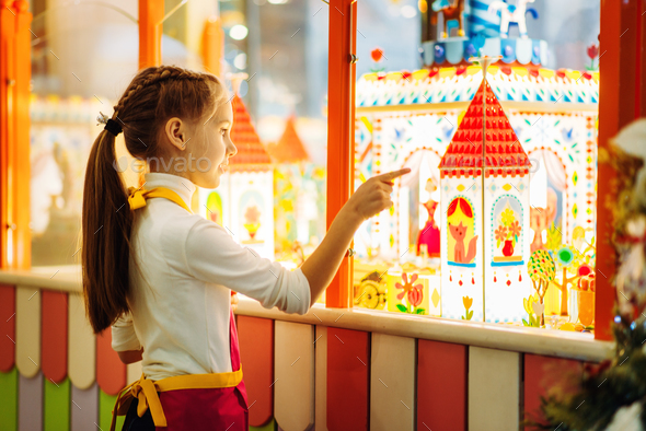 Girl watching on showcase with caramel buildings - Stock Photo - Images