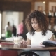 A Girl with a Multi-ethnic Appearance Drinks Coffee in a Coffee House and Prints a Message on Her - VideoHive Item for Sale